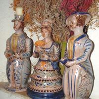 Tre lumere siciliane riccamente decorate posizionate sul camino di un antico casale