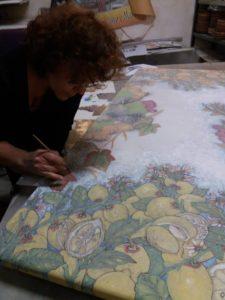 La ceramista Laura Talio che decora un tavolo in pietra lavica