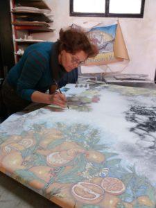 La pintora y ceramista Laura Talio decora una mesa de piedra de lava con limones, naranjas, granadas, uvas y higos chumbos.